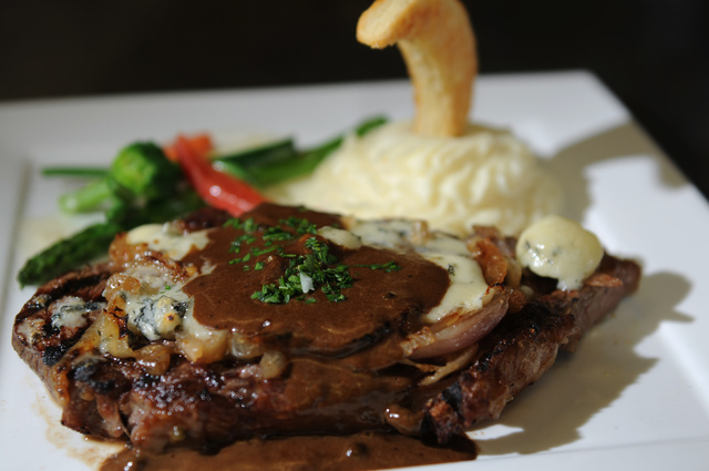 A pan roasted rib eye steak with rockford cheese and bourbon sauce is seen served with truffled mashed potatoes and vegetables at Bernard's Bistro in Henderson, Nev., Saturday, May 17, 2014. (Erik ...
