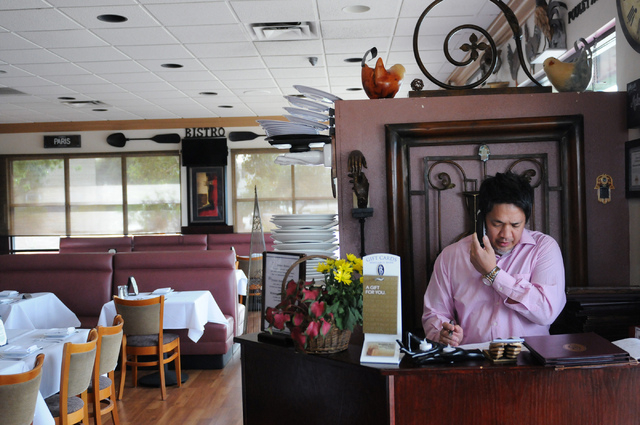 General manager Roger Mora answers the phone during dinner service at Bernard's Bistro in Henderson, Nev., Saturday, May 17, 2014. (Erik Verduzco/Las Vegas Review-Journal)