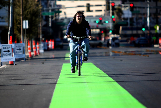Curt Marquardt rides a bicycle along a brightly-painted green bike lane on Ogden Avenue near 9th Street in downtown Las Vegas on Monday, Feb. 18, 2013. (Jessica Ebelhar/Las Vegas Review-Journal)
