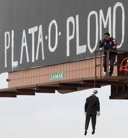 """An El Paso, Texas police officer checks a makeshift mannequin Thursday, May 22, 2014, which was left hanging on a billboard along with the message, """"silver or lead"""" in Spanish, a threat heard in M ..."""