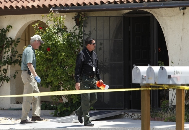 Investigators walk by a home where a dead body was found at 2841 E. Florence Lane in Las Vegas Tuesday, May 6, 2014. (John Locher/Las Vegas Review-Journal)