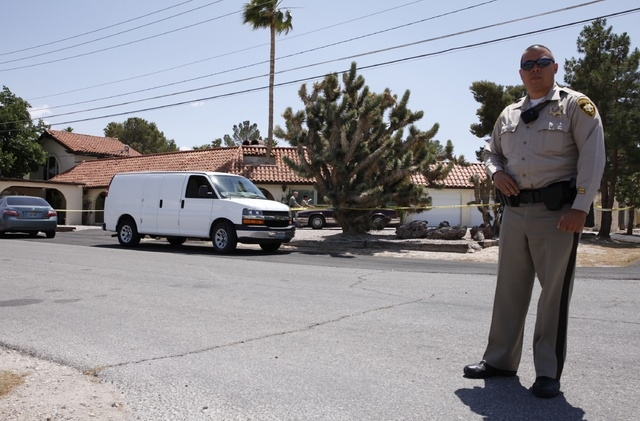 A Las Vegas police officer stands by a home where a dead body was found at 2841 E. Florence Lane in Las Vegas Tuesday, May 6, 2014. (John Locher/Las Vegas Review-Journal)