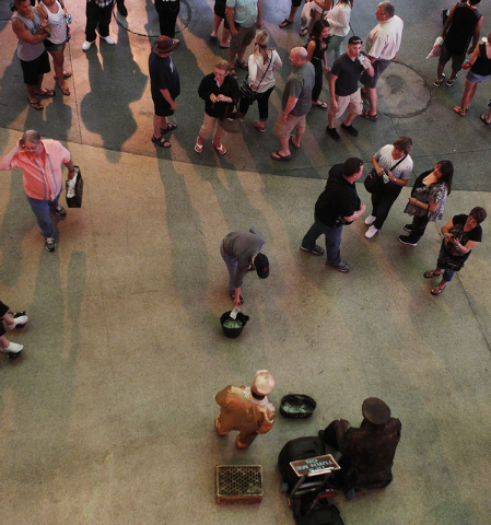 Goldmine, lower left in gold suit, and his partner Gizmo receive tips from people who gathered to see them perform at the Fremont Street Experience in Las Vegas on Thursday, May 22, 2014. (Jason B ...