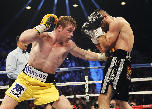 Saul Canelo Alvarez, left, hits Alfredo Angulo during their Super Welterweight fight at the MGM Grand Garden Arena in Las Vegas on March 8. (Jason Bean/Las Vegas Review-Journal)