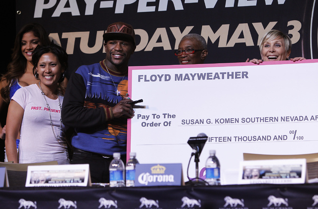 Boxer Floyd Mayweather Jr. makes a presentation of a $15,000 charitable donation to the Susan G. Komen foundation during a press conference prior to his fight against Marcos Maidana at the MGM Gra ...