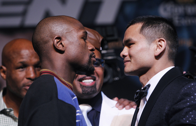 Boxers Floyd Mayweather Jr., left, faces off against Marcos Maidana during a press conference prior to their fight at the MGM Grand in Las Vegas on April 30, 2014.  Seen in the background, from le ...