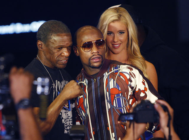 Boxer Floyd Mayweather Jr., middle, poses for a photo with his father and trainer Floyd Mayweather Sr. after arriving at the MGM Grand prior to his fight against Marcos Maidana in Las Vegas on Tue ...