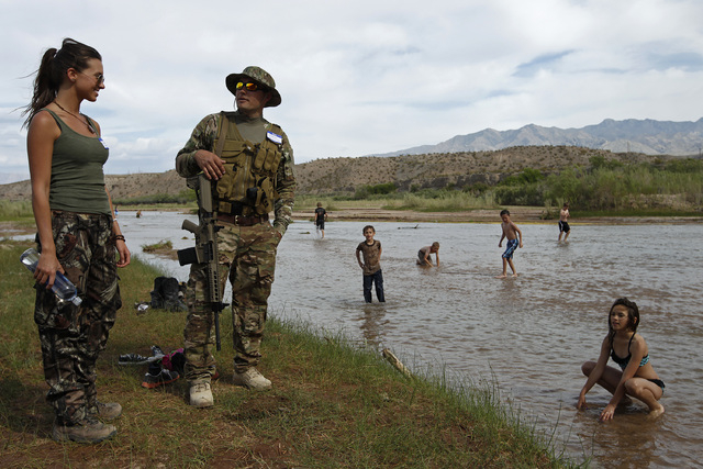 Jennifer Scalzo, left, and her husband Anthony Scalzo stand by the Virgin River during a rally in support of Cliven Bundy near Bunkerville, Nev. Friday, April 18, 2014. (John Locher/Las Vegas Revi ...