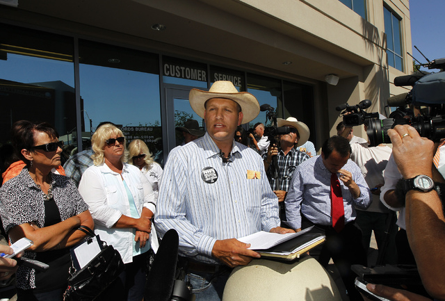 Ammon Bundy, middle, son of embattled rancher Cliven Bundy, reads a statement as the Bundy family and their supporters file official complaints and press charges against federal law enforcement ag ...