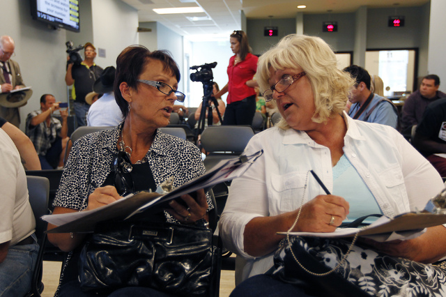 From left, Margaret Houston and Lillie Spencer, sisters of rancher Cliven Bundy, fill out the paperwork to file official complaints and press charges against federal law enforcement agents stemmin ...