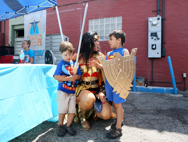 Ben Foster, 3, left, and Joe Foster, 5, right, visit with Lara Duffin who is dressed as Wonder Woman during a Critical Care Comics fundraising event on Free Comic Book Day outside HellPop! comic s ...
