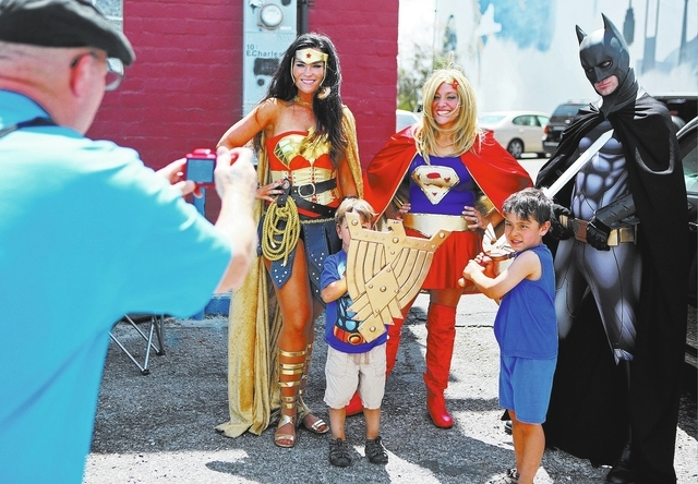 Lara Duffin dressed as Wonder Woman, from left, stands with Ben Foster, 3, Tia Golden dressed as Supergirl, Joe Foster, 5, and Cody Strohl dressed as Batman for a personal photograph during a Crit ...