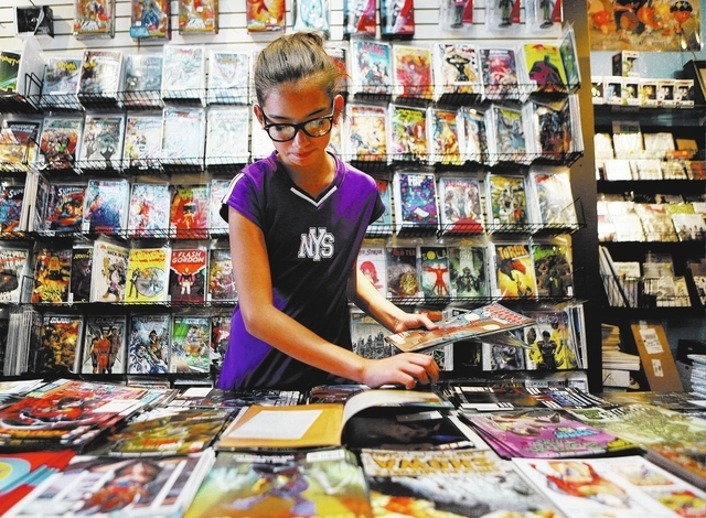 Kaylee Crafton, 11, looks through free comic books at a Free Comic Book Day event at HellPop! comic store at the Arts Factory Saturday, May 3, 2014, in Las Vegas. HellPop! joined Critical Care Com ...