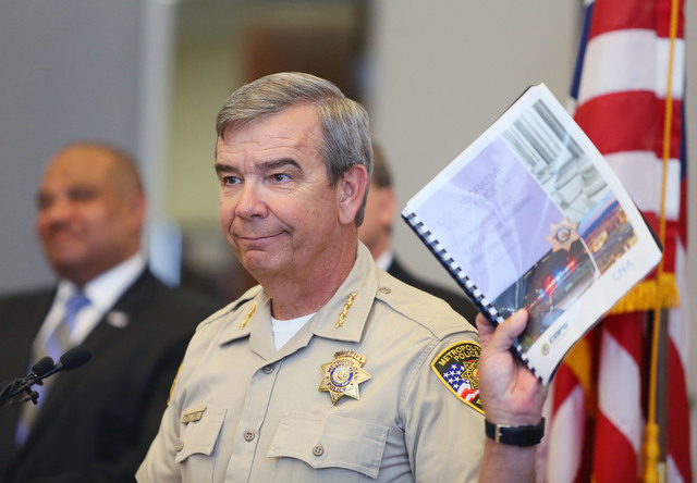 Clark County Sheriff Doug Gillespie holds up a report during a news conference at the Lloyd D. George U.S. Courthouse Wednesday, May 21, 2014, in Las Vegas. The Office of Community Oriented Polici ...