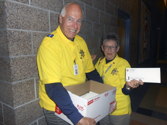 Howard Jenkins and his wife, Lynda, pass out envelopes May 6 at the Metropolitan Police Department's Northwest Area Command, 9850 W. Cheyenne Ave., providing information for drivers in the event ...