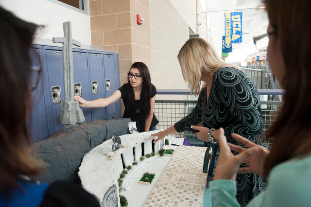 Sunrise Mountain High School advanced placement Spanish student Alondra Diaz, center, adjusts her group's model, which depicts El Valle de los Caidos, a monument in Spain, as part of a class pro ...