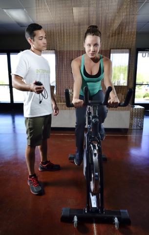 Intermix Fitness co-owners Almas Meirmanov, left, and Katia Dmitrieva are shown during a cardio mid-tempo demonstration on a stationary bike at their gym at 1770 W. Horizon Ridge Parkway in Hender ...