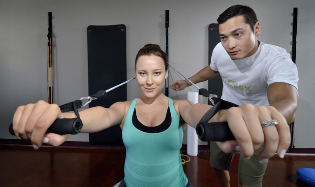Intermix Fitness co-owners Katia Dmitrieva, left, and Almas Meirmanov are shown during a front chest press with resistance bands exercise demonstration at their gym at 1770 W. Horizon Ridge Parkwa ...