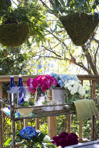 In this photo provided by Brian Patrick Flynn/HGTV.com, for the design of the HGTV.com Spring House outdoor dining deck, the designer Flynn made entertaining easy with a weather-resistant mobile b ...