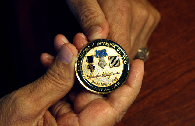 Korean War ex-POW Gene Ramos holds a medallion that commemorates his friend and comrade Hirsohi Miyamura during an interview at his home in Las Vegas on Thursday, May 22, 2014. He was captured as  ...