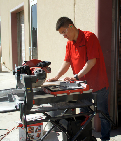 Photo by Art Nadler  Jamie Mitchell, a third-year landscape/architecture student, cuts Wedi board with a band saw.