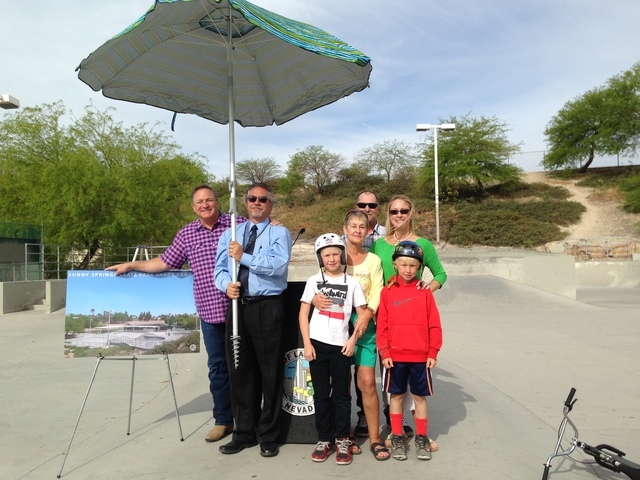 Councilman Steve Ross, from left, and Michael Vlaovich, architectural project manager with the Las Vegas Public Works Department, pose for a photograph with Dalton Taylor, 10, and his family, cloc ...