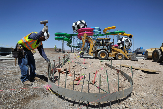 Construction worker Jose Lopez pounds stakes to support concrete forms beneath one of the slide towers at Cowabunga Bay water park along Galleria Drive in Henderson on Monday, May 12, 2014. The 23 ...