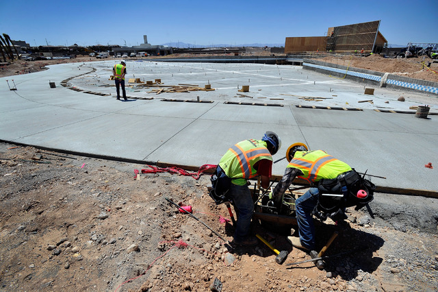 Construction workers Conrado Escobar, left, and Juan Lopez set a foundation support for shade awnings near the wave pool at Cowabunga Bay water park along Galleria Drive in Henderson on Monday, Ma ...