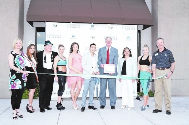 City officials join Almas Meirmanov, centered, at the ribbon cutting ceremony of Intermix Fitness Elite on April 21. (Special to View)