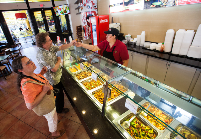Maria Carillo hands a sample of orange chicken to Mel Mochan, as his wife Bonny looks at the menu, at International Eatery, a restaurant which features Mexican, Italian and Asian food stations at  ...