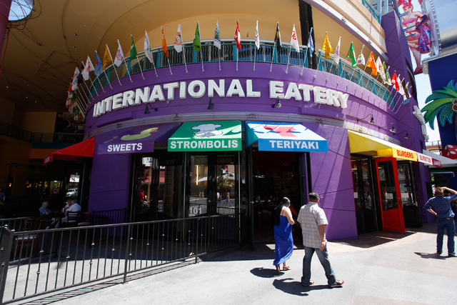 People walk past International Eatery, a restaurant which features Mexican, Italian and Asian food stations at the Fremont Street Experience next to SlotZilla in downtown Las Vegas on April 24. (C ...