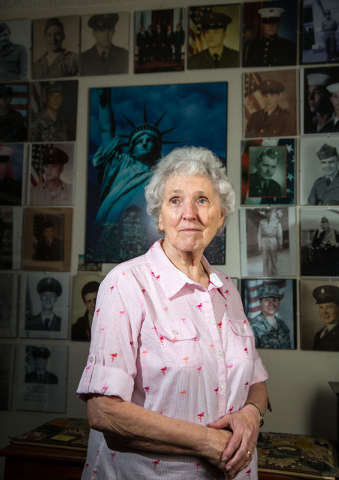 Phyllis Hebert, 81, poses with her collection of photos at her Las Vegas home Friday, May 23, 2014. Hebert dedicated a wall in her home to photos, honoring family and friends who have served in th ...