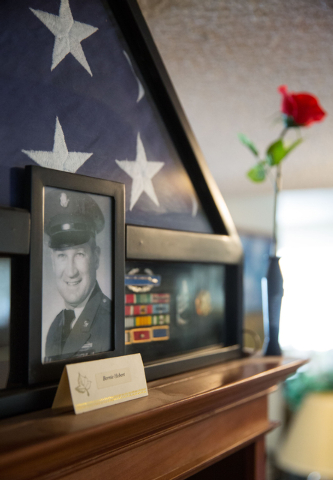 A memorial for Bernard Hebert is displayed inside the home of his wife, Phyllis Hebert, Friday, May 23, 2014. After Bernard Hebert's death in 2005, his wife collected photos of friends and family  ...