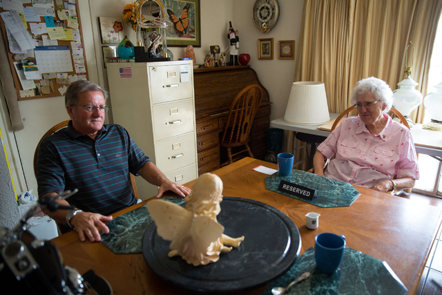 Gene Demeter, left, and Phyllis Hebert talk inside Hebert's Las Vegas home Friday, May 23, 2014. Hebert dedicated a wall in her home to photos, honoring family and friends - including friend Demet ...