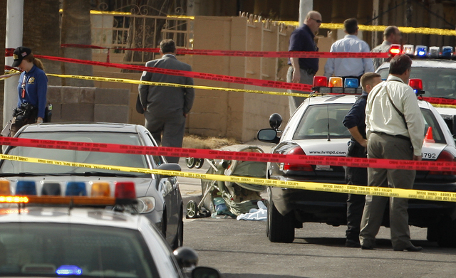 Las Vegas police investigate an overturned stroller where a hatchet-wielding man brutally attack a woman and her baby on the 1600 block of San Pedro Ave., on Thursday, Feb. 11, 2010, in Las Vegas. ...