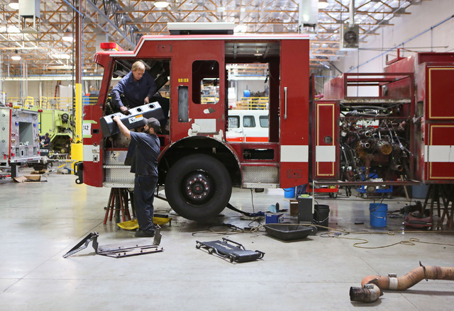 Mike Laqua, left, and Eduardo Pacheco work on a fire engine for a fire department in Little Rock, Ark. at Firetrucks Unlimited Friday, May 30, 2014, in Henderson. Firetrucks Unlimited, a family-ow ...