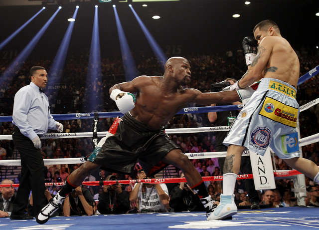 Floyd Mayweather Jr. hits Marcos Maidana during their welterweight title bout at the MGM Grand in Las Vegas Saturday, May 3, 2014. (Jason Bean/Las Vegas Review-Journal)
