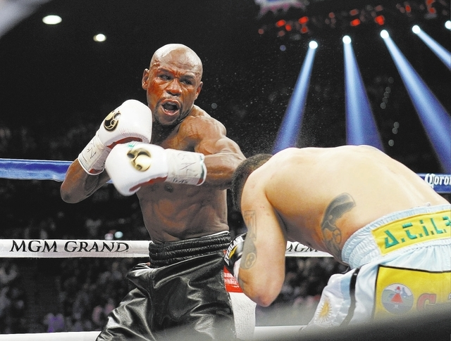Floyd Mayweather Jr. misses landing a punch against Marcos Maidana during their welterweight title bout at the MGM Grand in Las Vegas Saturday, May 3, 2014. Mayweather was bloodied above his left  ...