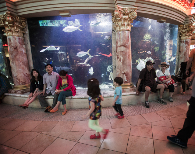 People gather around the aquarium at The Forum Shops at Caesars on Monday, May 12, 2014.  A mix of new retail stores and restaurant will be opening soon in the 22-year-old mall located in Caesars. ...