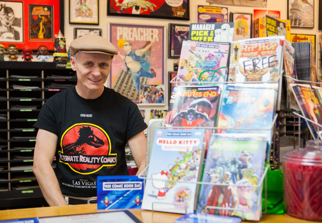 Store owner Ralph Mathieu poses with a selection of comics slated to be given out as part of Free Comic Book Day at Alternate Reality Comics, 4110 S. Maryland Parkway, in Las Vegas on Wednesday, A ...