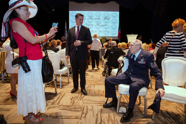 Debbie Bush, left, takes a photo of her neighbor ,Davis B. Leonard, 91, at the Silverton on Friday, May 30, 2014. Leonard was awarded the Legion of Honor for his service in World War II. (Samantha ...