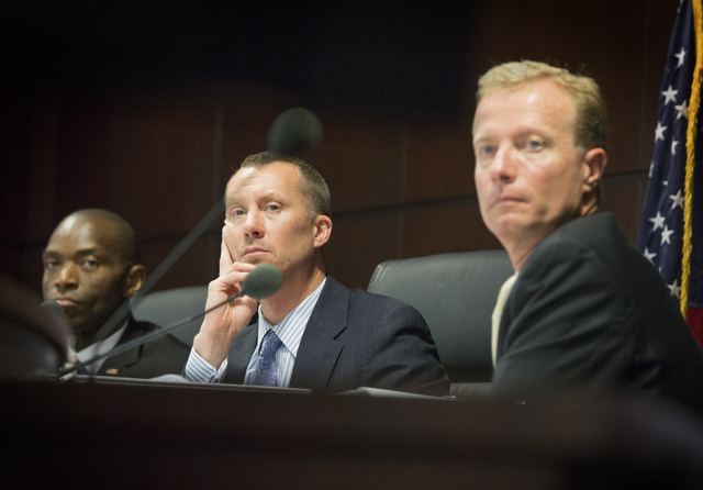 Nevada Gaming Control Board Members Terry Johnson, left, A.G. Burnett and Shawn  Reid watch a video presentation by Resorts World Las Vegas during a suitability hearing at  Sawyer Building on Wedn ...