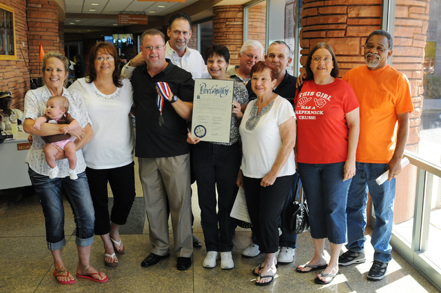 Mike Elgas, third from left, stands with his family and friends after a ceremony recognizing him as a good Samaritan during a meeting at the Commission Chambers inside the Clark County Government  ...