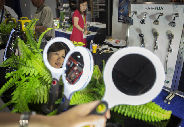 Irene Wong holds a beauty mirror at the Lomak booth at the National Hardware Show in the Las Vegas Convention Center on Tuesday, May 6, 2014. More than 27,000 people are expected to attend the tra ...