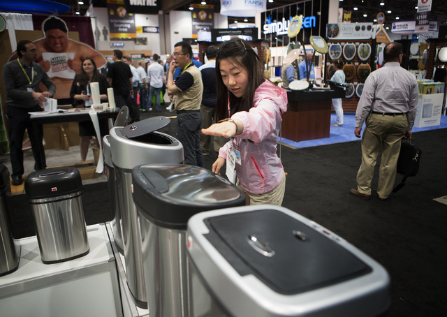 A woman actives a motion sensor trash can at the Ninestar  booth during the National Hardware Show in the Las Vegas Convention Center on Tuesday, May 6, 2014. More than 27,000 people are expected  ...