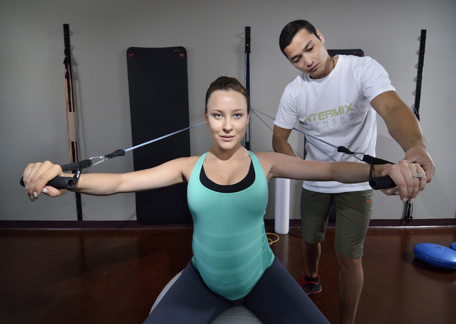 Intermix Fitness co-owners Katia Dmitrieva, left, and Almas Meirmanov are shown during a wide-arm chest press with medicine ball and resistance bands exercise demonstration at their gym at 1770 W. ...