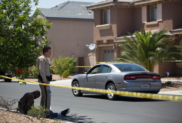 A man sits handcuffed while homes are blocked by police tape on Turtle Ridge Avenue in a neighborhood near Las Vegas Boulevard and Starr Avenue on Monday, May 12, 2014. Police found a person wound ...