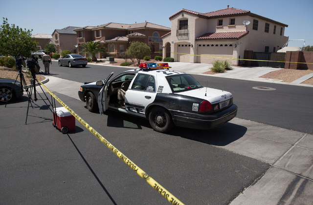 Homes are blocked by police tape on Turtle Ridge Avenue in a neighborhood near Las Vegas Boulevard and Starr Avenue on Monday, May 12, 2014. Police found a person wounded by a gunshot and suspect  ...