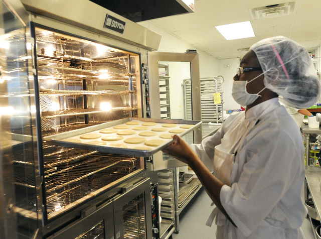 Raya Allen puts a tray of sugar cookies in the oven at Jadon Foods.  (Jerry Henkel/Las Vegas Review-Journal)