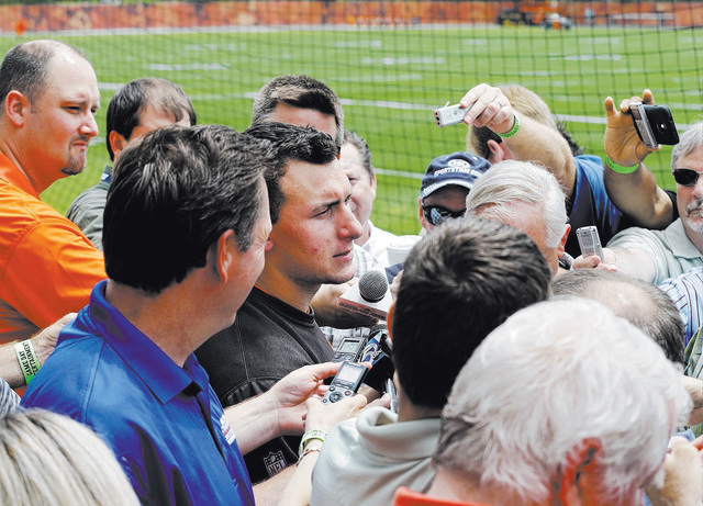 Writers crowd around Cleveland Browns quarterback Johnny Manziel, center, after an organized team activitiy at the NFL football team's facility in Berea, Ohio Wednesday, May 28, 2014. (AP Photo/Ma ...